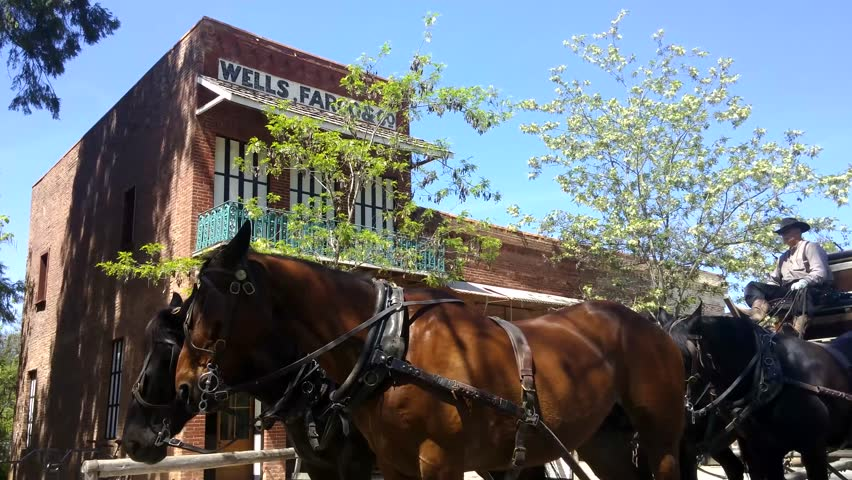 Columbia, California - April, 2015 - Stagecoach passing by a historic Well Fargo Building.