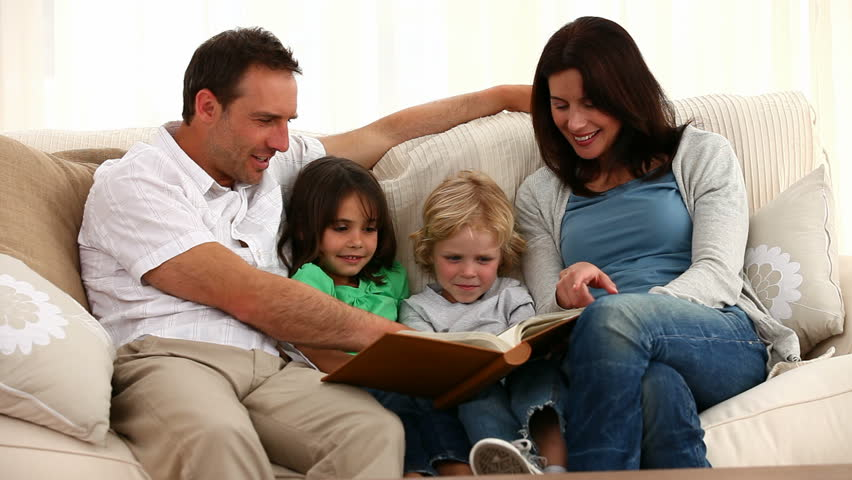 Cute family reading a book while sitting  on the sofa at home - HD stock video clip