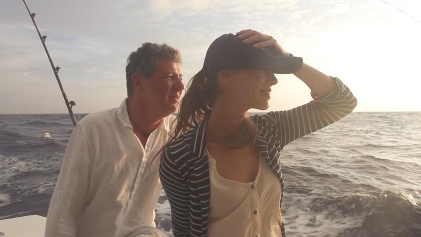 Slow Motion Of Couple Cruising Towards Sunset On Big Game Fishing Boat