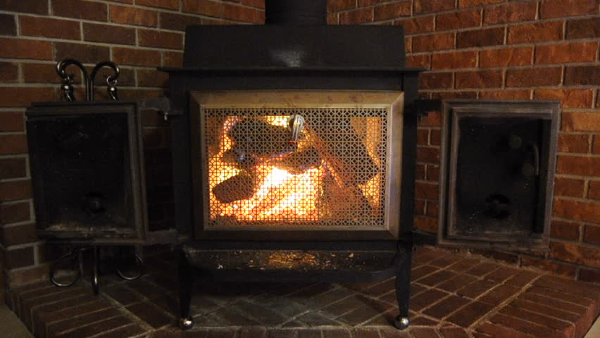 A Nice Comfortable Wood Stove Fireplace With A Fire Inside Against A Brick Wall In The Corner