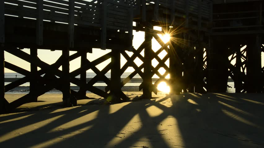 Beautiful romantic sunset on the beach of the north sea through the stairs of an impressive pile-work