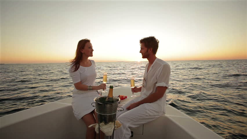 young honeymoon couple drinking champagne on a boat at sunset  - HD stock footage clip