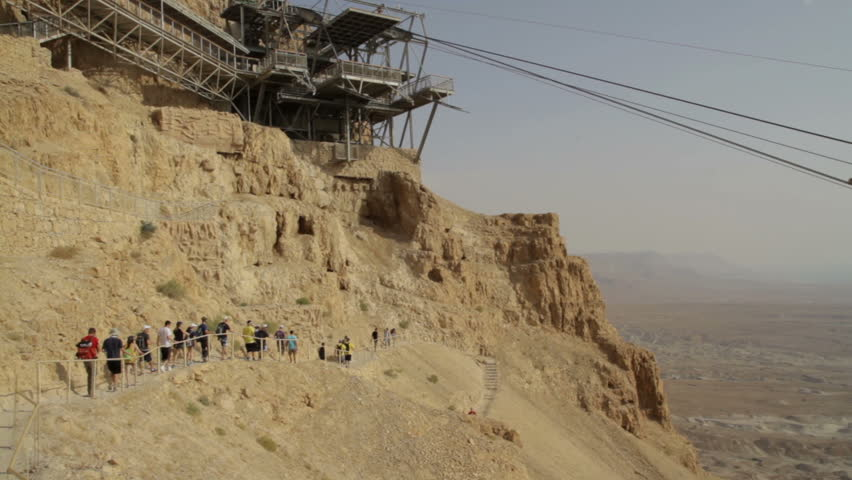 ?able car way at Masada fortress. Tourists walking around.