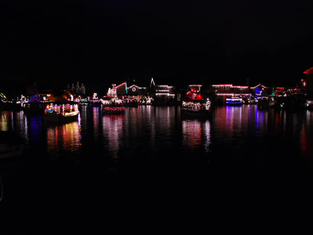 Boat parade on a lake with Christmas lights reflecting on the water - PAL.  - SD stock video clip