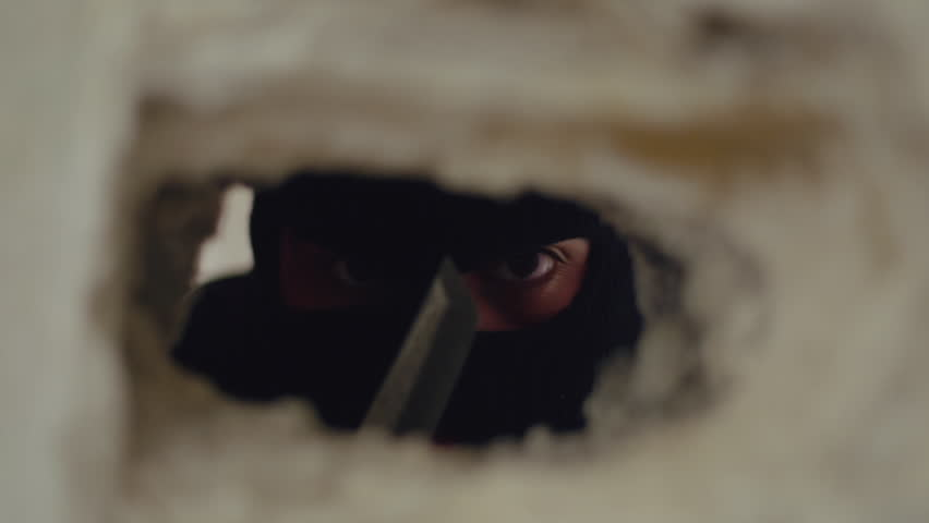 Ninja assassin,masked killer with knife lurking behind a crack in the wall.A ninja assassin lurks behing a crack in the wall with eyes wide open.Close up slider tracking shot.
