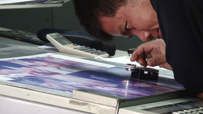 Offset print technician checks details of a test sheet with a magnifying glass. All the photographic images in this clip are property released. - HD stock video clip