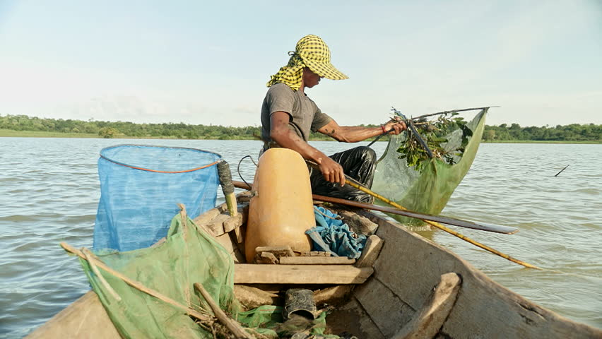 Fisherman lifts his net up and hangs a bait ball up for prawn fishing. The shrimp net is square that was made by four bamboo sticks, southeast asia, Cambodia.