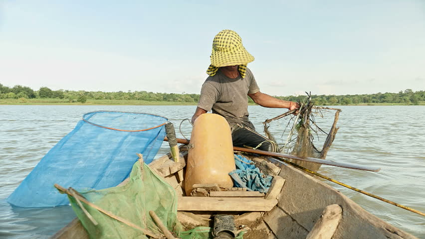 Fisherman  hangs a bait ball up for prawn fishing. The shrimp net is square that was made by four bamboo sticks, southeast asia, cambodia
