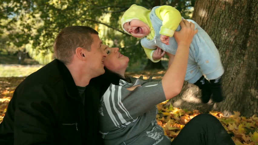 Happy Family Holding Their Child in the park - HD stock footage clip