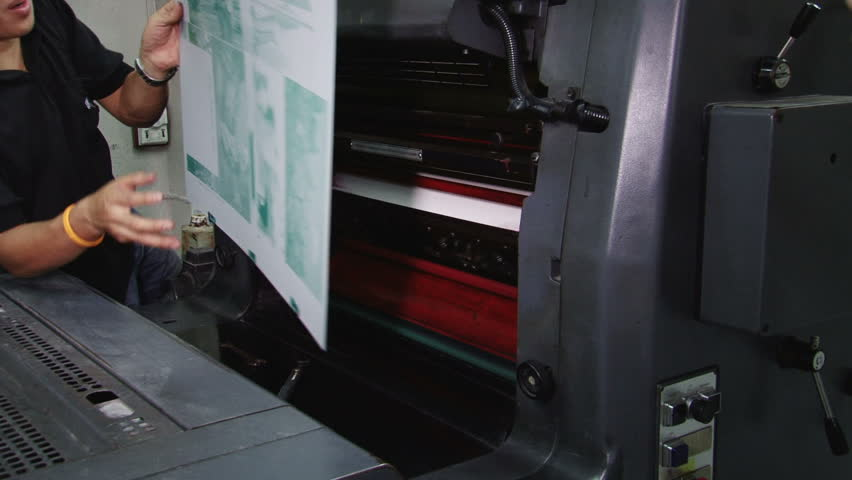 Printer fixing a plate onto the print machine cylinder. All images in the clip are property released. - HD stock footage clip