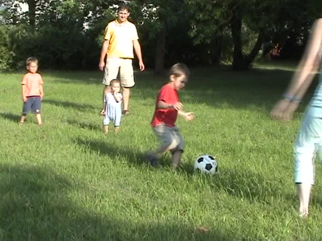 Happy family with three children playing soccer in the park - SD stock footage clip