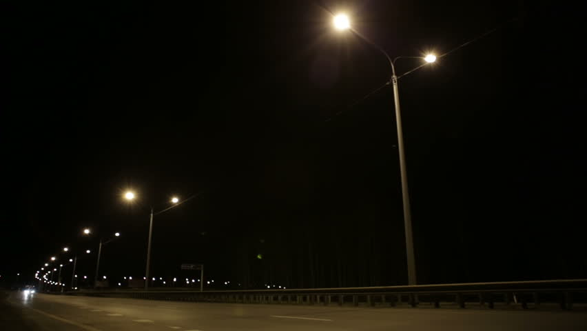 Cars go on night road. Night road is lit by street lamps and cars headlights