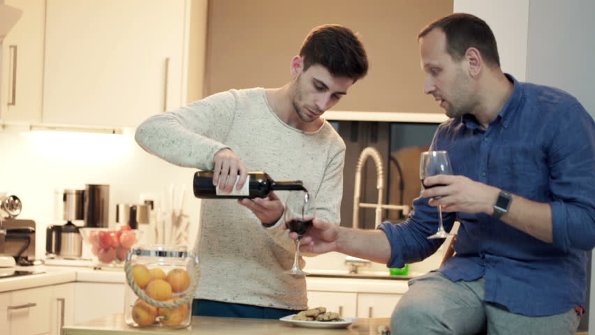 Young, handsome friends talking and drinking wine in the kitchen at home