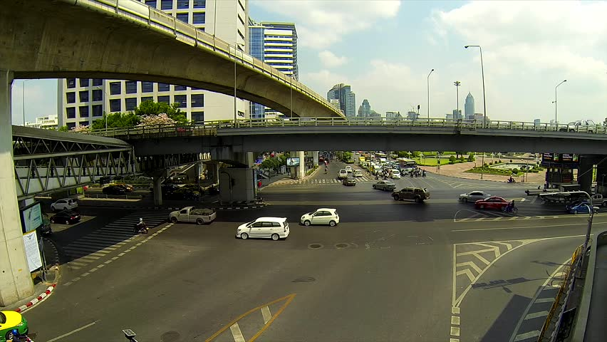 BANGKOK - March 2015: Bangkok's traffic with BTS sky trains passing by. Silom intersection. - HD stock footage clip