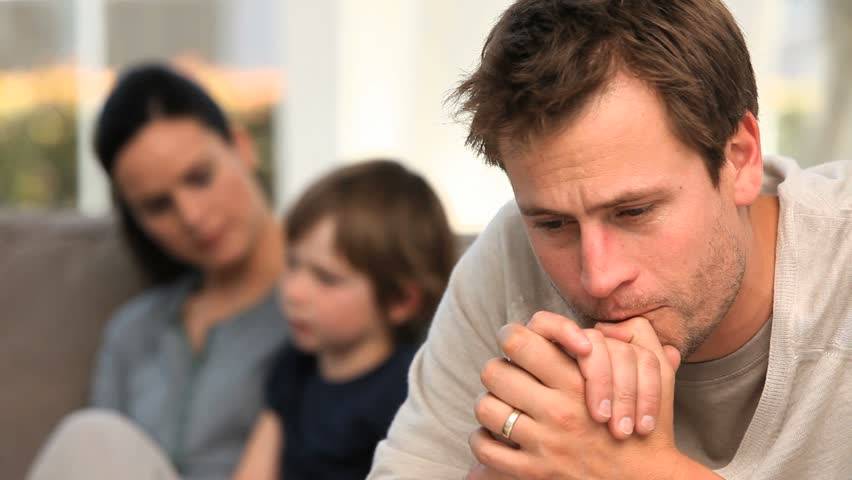 A man is worrying while his family is on the sofa - HD stock footage clip