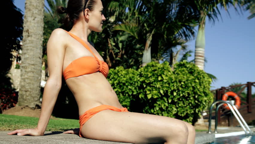 A beautiful woman sunbathing by the pool  - HD stock footage clip