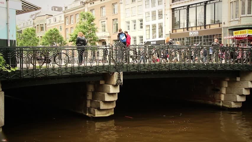 AMSTERDAM, NETHERLANDS - JUNE 14, 2015: Time Lapse Tram Amsterdam over the bridge with tourists ans stores in Amsterdam, Netherlands 14 June 2015