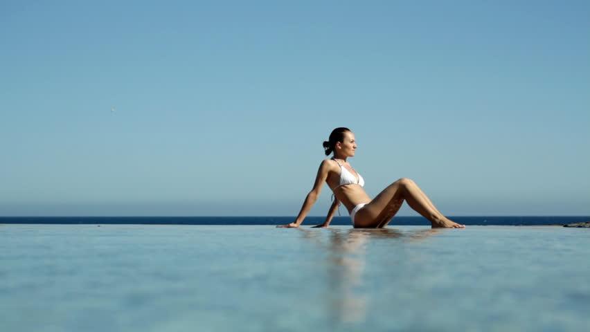 A beautiful woman sunbathing by the sea - HD stock footage clip