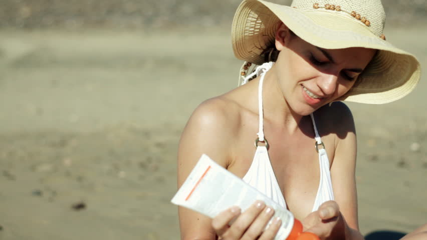 Woman on the beach applying protection lotion - HD stock footage clip
