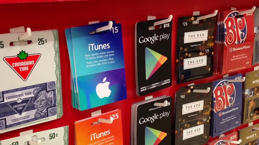Coquitlam, BC, Canada - June 26, 2015 : Man picking fifteen dollar google play gift card inside supermarket