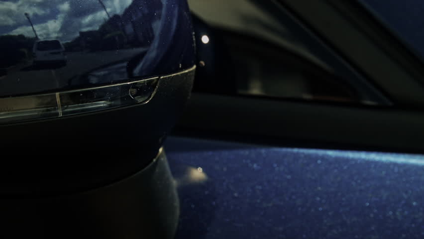 Car door mirror indicator flashing HD stock footage. A blue door mirror with a built in direction indicator flashing in orange light. ProRes.