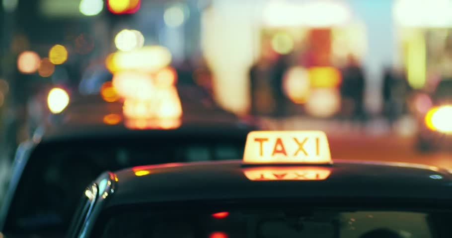 Long row of taxi cabs arriving and picking up passengers on city street at night. Blurred background of modern town