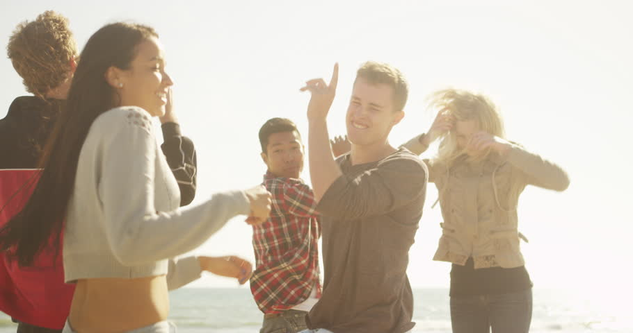Happy group of multi ethnic friends dancing together on the beach