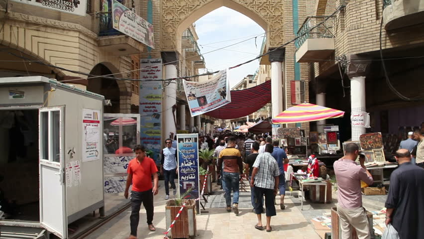 BAGHDAD, IRAQ - MAY 2015: People at Mutanabbi Street's entrance in Baghdad. Mutanabbi Street where writers and intellectuals meet is the historic center of Baghdad bookselling