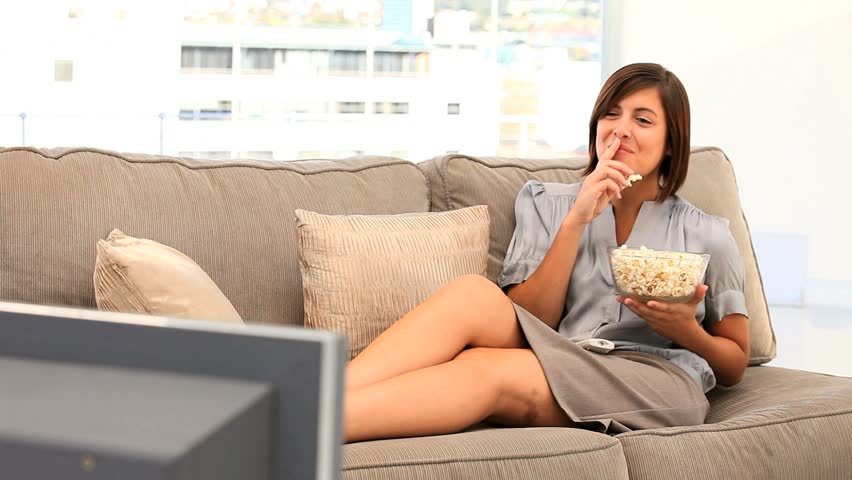 Pretty lady watching tv with popcorn in her living room - HD stock footage clip