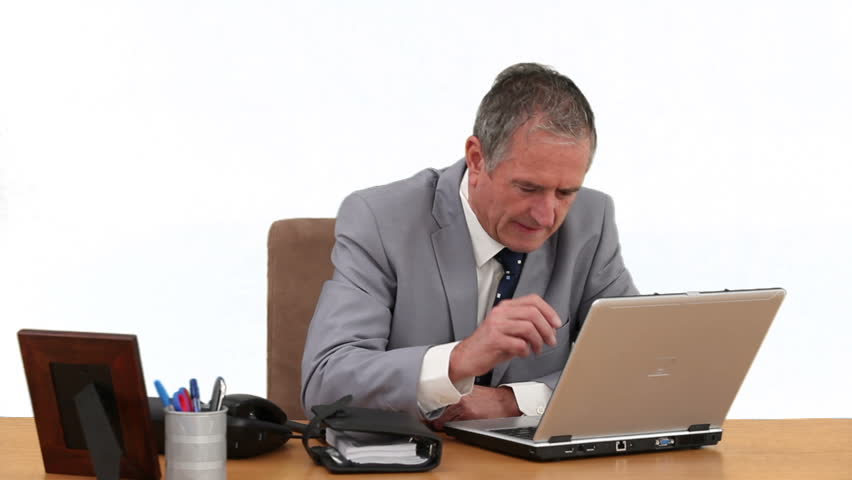 Elderly businessman in gray suit working on his computer at his desk - HD stock video clip