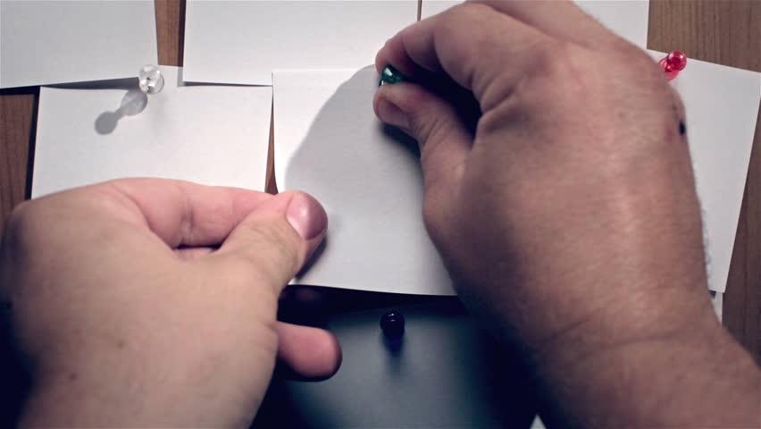 Hand attaches white sticker on wood message board