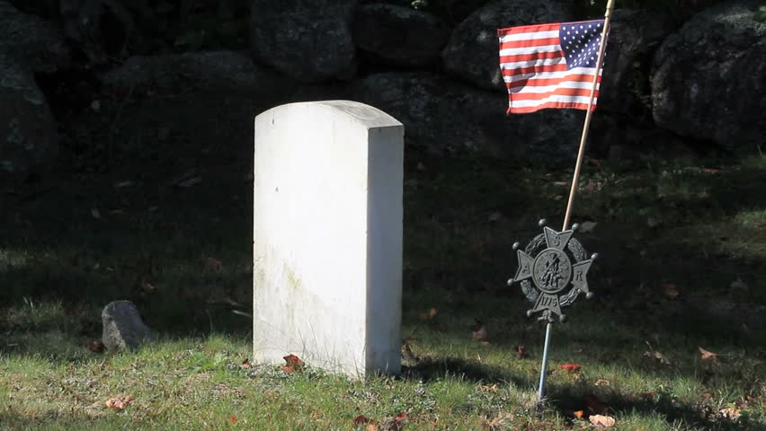 Revolutionary and Civil War Grave yard. Close up of blank marble tombstone with copy space. United States of America flag blowing in strong wind