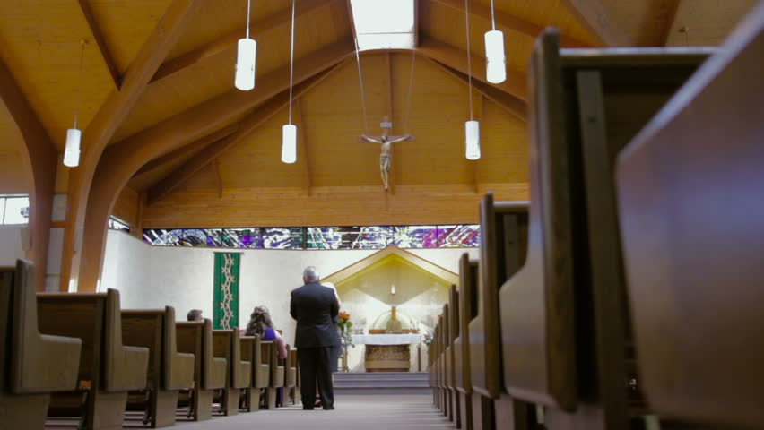 Interior of a catholic church as people walk in. - HD stock footage clip