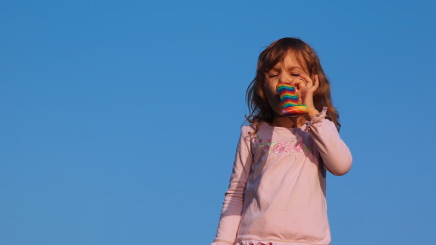 nice little girl blows party blower on blue sky - HD stock footage clip