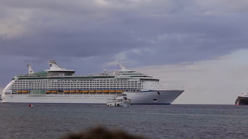 GRAND CAYMAN, CAYMAN ISLAND - 20 JULY 2012: tender boats are sailing aside of Voyager of the Seas large cruise ship