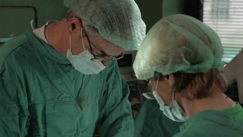 Surgeon making incision on the patient with electric surgical knife, tilt down. Surgical team performing operation in hospital room. Surgery on specialized clinic. Patient lying on operating table.