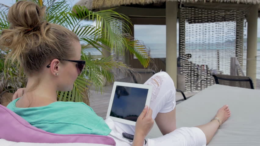 Woman reading a book on the beach stock footage video for Tablet hotel booking
