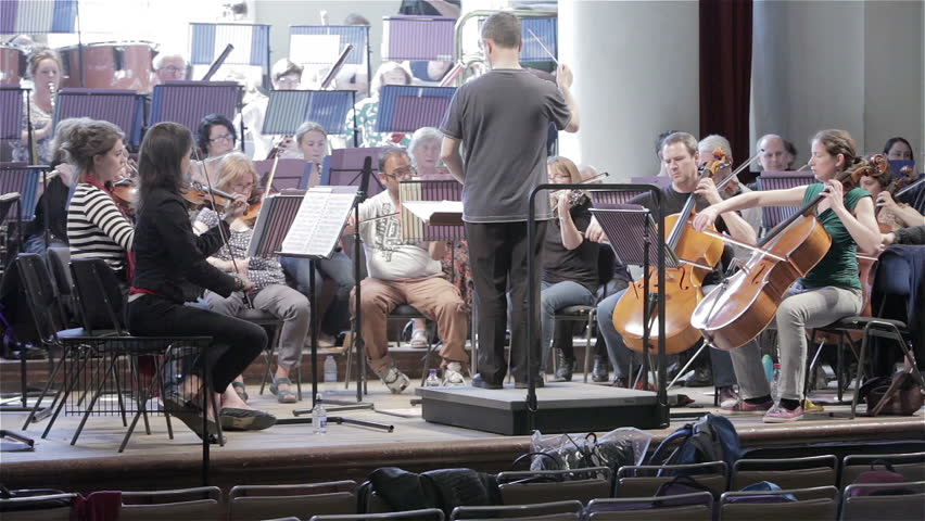 LONDON, UK - 8 JUNE 2013: Candid video footage of a conductor of a classical symphony orchestra at work with the surrounding front desk string players in view.