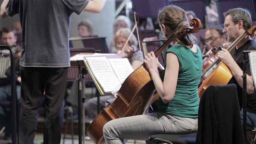LONDON, UK - 8 JUNE 2013: Candid video footage of a slow pan across the cello section of a classical symphony orchestra during rehearsal.