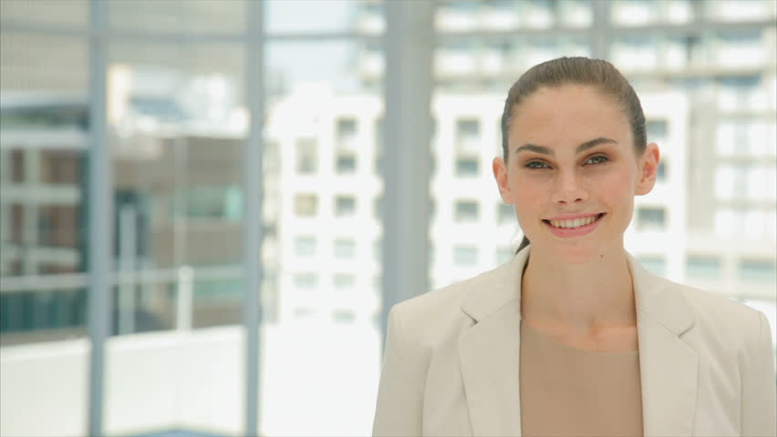 Lockdown shot of beautiful young businesswoman smiling. Businessmen are shaking hands in background. Young professionals are in brightly lit office.