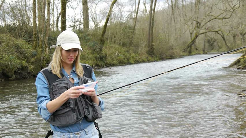 Woman in river using fishing rod stock footage video for River fishing pole