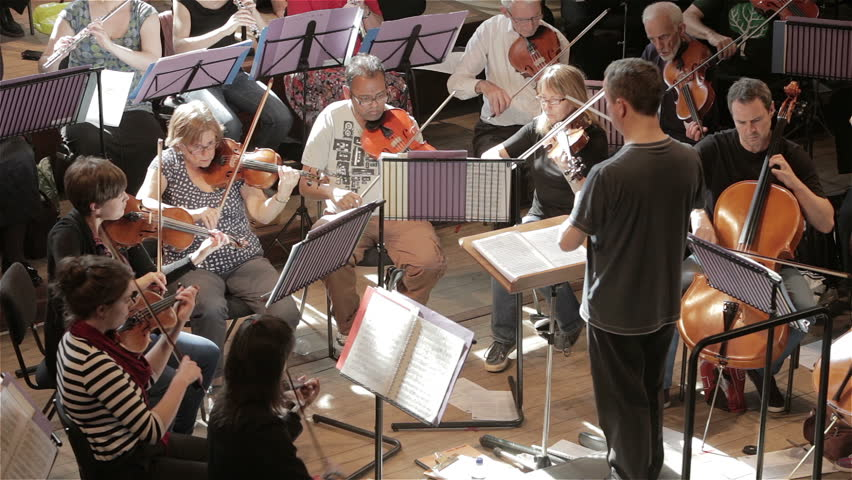 LONDON, UK - 8 JUNE 2013: Candid video footage looking down onto a conductor leading a classical symphony orchestra during a rehearsal.