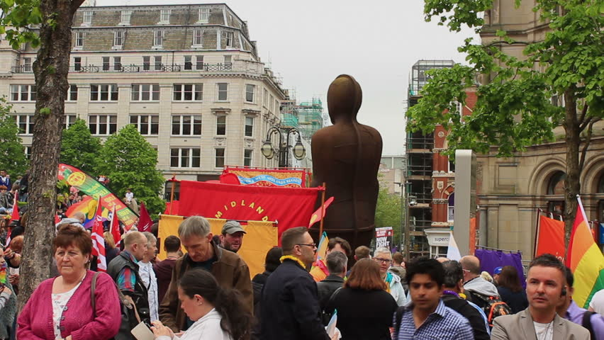 Crowd of people gathering by The Iron Man statue during Birmingham Gay Pride 2015. This is a statue by Antony Gormley, in Victoria Square, Birmingham, England.
