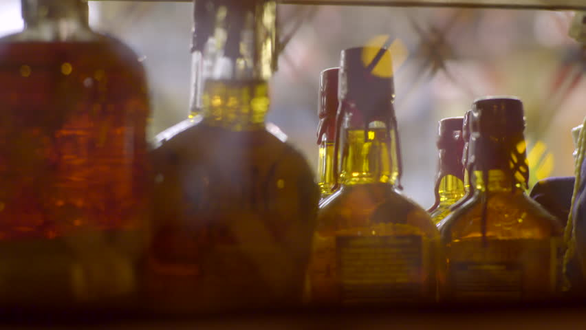Row Of Liquor Bottles On A Liquor Store Shelf, Can't See Labels (Shot From Outside Looking In)