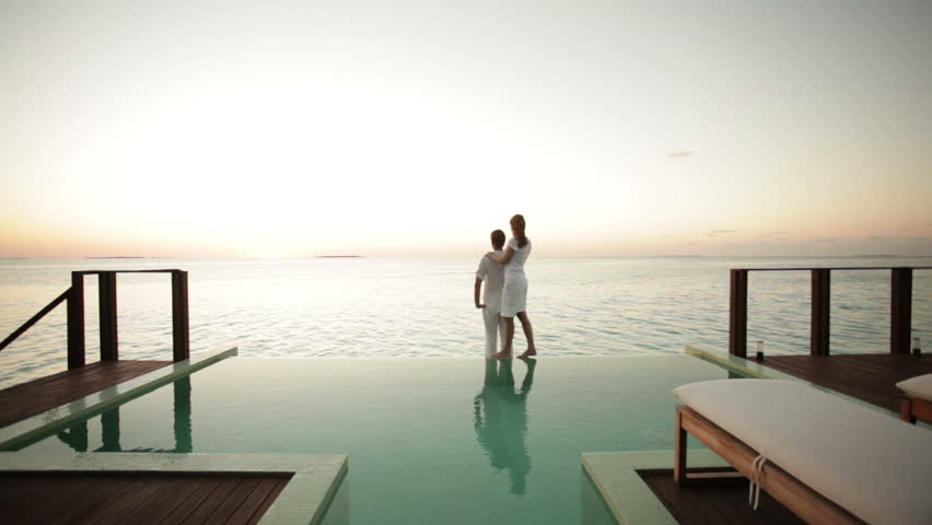 couple in white on private pool watching sunset over lagoon