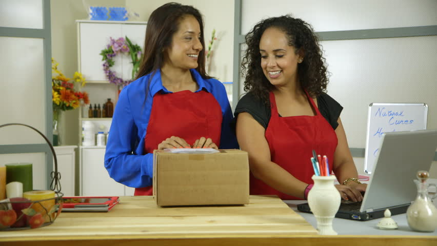 Two lovely Latin American small shop owners using laptop computer stop working and smile for camera. - HD stock footage clip