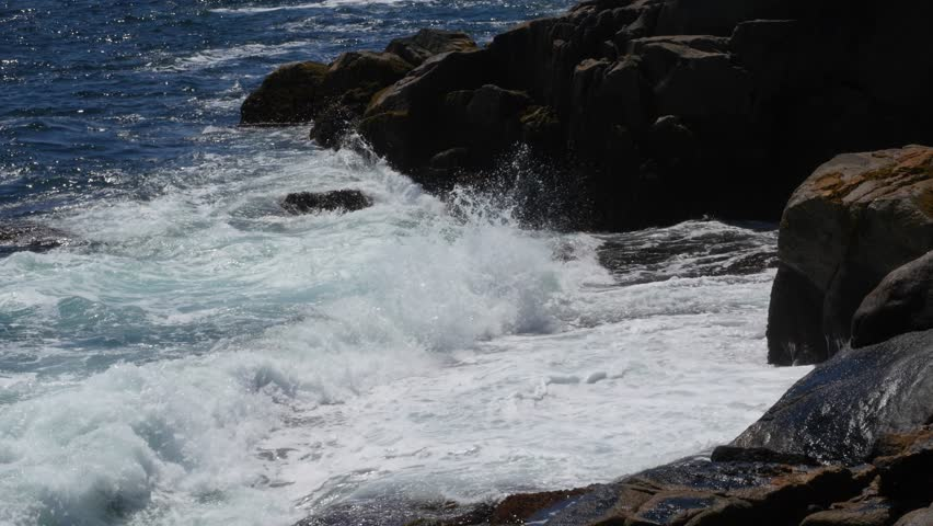 storm waves breaking against rocks on ocean shoreline