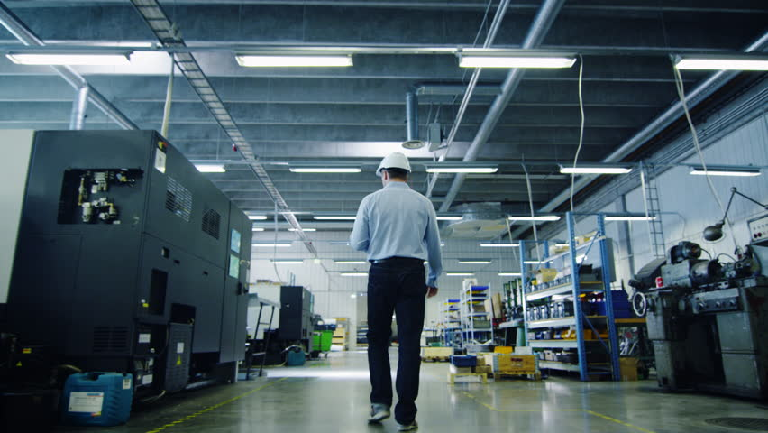Engineer in Hard Hat is Walking Through Factory. Back View. Shot on RED Cinema Camera in 4K (UHD).