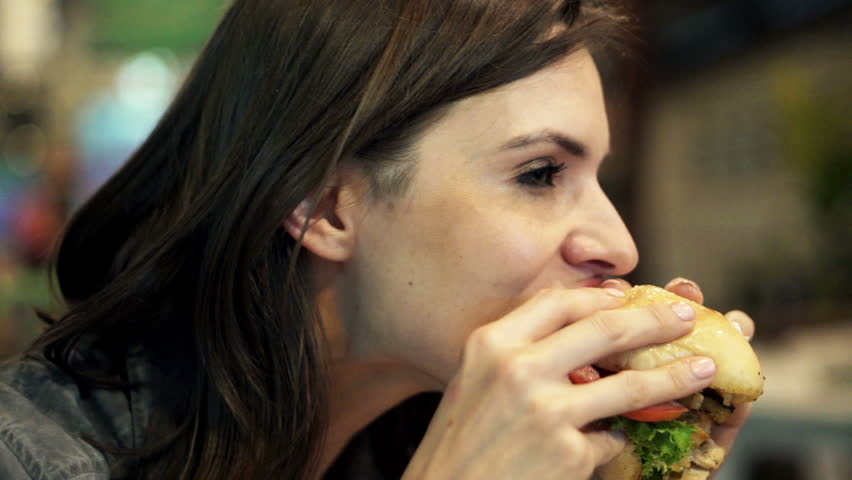 Young woman eating fast food, hamburger in cafe