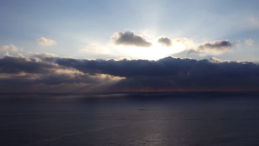 Time lapse footage with zoom out motion of morning sun ray through heavenly cloudscape over sea horizon